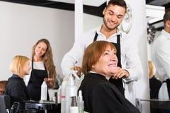 A mulher corta o cabelo com barbeiro Imagens de Stock