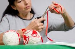 A mulher corta uma fita vermelha com tesouras para fazer uma curva para o christma Foto de Stock