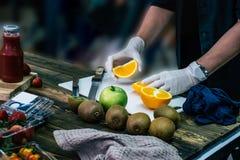 A mulher cortou a laranja com a faca com o assistente no w fotografia de stock