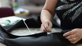 A mulher costura o caso em uma poltrona do couro vídeos de arquivo
