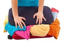 A mulher crammed completamente da roupa na mala de viagem vermelha Fotos de Stock Royalty Free