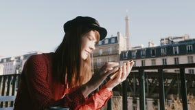 A mulher criativa bonita feliz do trabalhador sorri usando o app do mensageiro do smartphone no balcão da manhã com opinião da to vídeos de arquivo