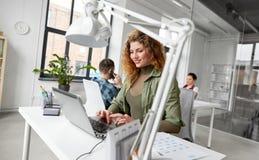 Mulher criativa com o portátil que trabalha no escritório imagens de stock