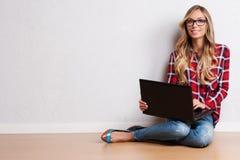 Mulher criativa nova que senta-se no assoalho com portátil / B ocasional fotografia de stock royalty free