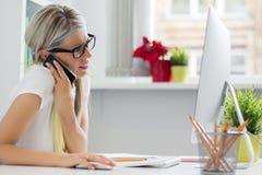 Mulher criativa que fala no telefone no escritório Fotografia de Stock Royalty Free