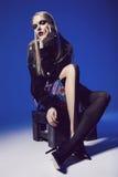 Mulher criativa que senta-se na parte superior preta e em calças justas pretas Imagem de Stock Royalty Free