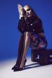 Mulher criativa que senta-se nas calças justas e nas sapatas nos saltos Fotos de Stock