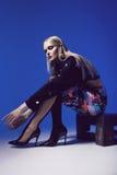 Mulher criativa que senta-se nas sapatas nos saltos e em calças justas pretas Fotografia de Stock Royalty Free