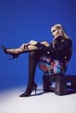 Mulher criativa que senta-se nas sapatas nos saltos e nas calças justas Imagens de Stock Royalty Free