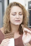 Mulher culpada na dieta que come a barra de chocolate em casa Fotos de Stock