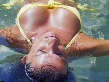 A mulher Curvy no roupa de banho que flutua na água e toma sol Imagem de Stock Royalty Free