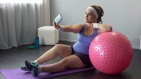 Mulher curvy presumido que faz o selfie no smartphone durante o exercício home fotografia de stock