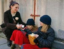 A mulher dá o dinheiro aos pedintes das crianças Fotografia de Stock Royalty Free