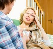 A mulher dá a seu amigo um comprimido de sono Imagens de Stock Royalty Free