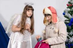 A mulher dá um presente a uma menina em um traje do anjo Imagens de Stock