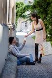 A mulher dá a um pedinte o dinheiro Fotografia de Stock Royalty Free