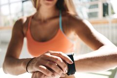 A mulher da aptidão após a sessão do exercício verifica resultados no smartwatch na aptidão app Conceito saudável do estilo de vi Fotos de Stock