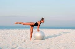 Mulher da aptidão com a bola do ajuste na praia fora Fotografia de Stock Royalty Free