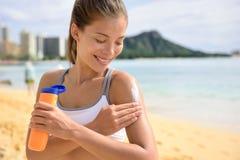 Mulher da aptidão da proteção solar que aplica a loção para bronzear imagem de stock royalty free
