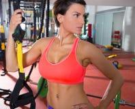 Mulher da aptidão de Crossfit que está no gym que guardara o trx imagens de stock