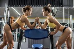 Mulher da aptidão de dois jovens, luta romana de braço no gym foto de stock royalty free