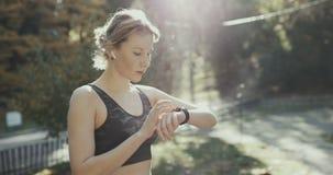Mulher da aptidão em fones de ouvido sem fio usando Smartwatch e em corridas na luz da manhã fotos de stock royalty free