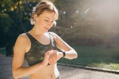 Mulher da aptidão em fones de ouvido sem fio usando Smartwatch e em corridas na luz da manhã imagens de stock
