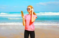 A mulher da aptidão escuta a música no fones de ouvido sem fio com smartphone Fotografia de Stock