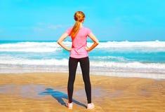 A mulher da aptidão está com ela para trás na praia perto do mar Foto de Stock Royalty Free