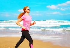 A mulher da aptidão está correndo ao longo da praia perto do mar Foto de Stock