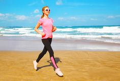 A mulher da aptidão está correndo na praia perto do mar Foto de Stock