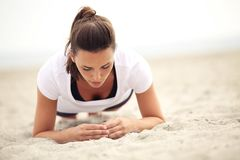 Mulher da aptidão na praia que faz exercícios do núcleo fotografia de stock