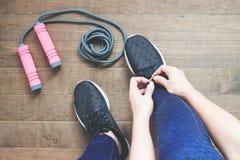 Mulher da aptidão que amarra sapatas no assoalho de madeira com equipamento de esporte, exercício, aptidão e dieta Estilo de vida Fotos de Stock