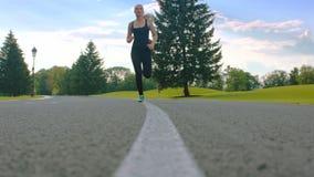 Mulher da aptidão que corre fora Treinamento fêmea do corredor na estrada do parque filme