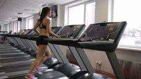 Mulher da aptidão que corre na escada rolante no gym dentro filme
