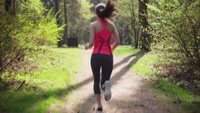 Mulher da aptidão que corre na floresta ensolarada da mola video estoque