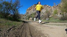 Mulher da aptidão que corre na natureza, paisagem da montanha, movimento lento filme