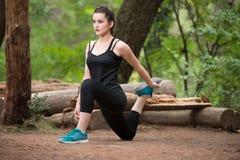 Mulher da aptidão que estica em Forest Area arborizado Imagens de Stock