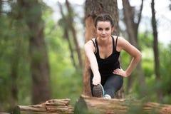 Mulher da aptidão que estica em Forest Area arborizado Foto de Stock Royalty Free