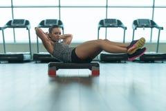 Mulher da aptidão que faz o exercício abdominal em deslizante Fotografia de Stock