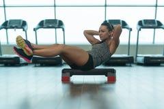 Mulher da aptidão que faz o exercício abdominal em deslizante Imagens de Stock Royalty Free