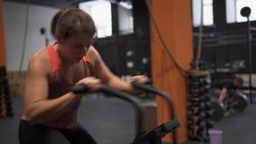 Mulher da aptidão que faz o exercício da bicicleta do ar no gym vídeos de arquivo