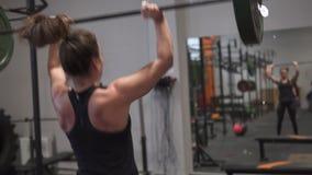 Mulher da aptidão que faz o exercício do levantamento de peso na frente do espelho no gym video estoque