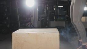 Mulher da aptidão que faz o exercício do salto da caixa no gym video estoque
