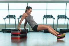 Mulher da aptidão que faz o exercício do tríceps em deslizante Foto de Stock