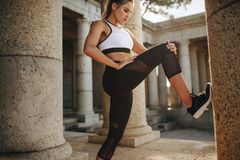 Mulher da aptidão que faz o exercício que estica seu pé com o apoio de uma coluna de pedra Treinamento do atleta fêmea que faz o  foto de stock
