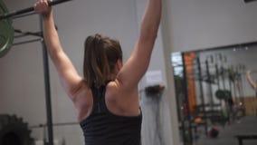 Mulher da aptidão que faz o exercício da imprensa do impulso do barbell na frente do espelho no gym vídeos de arquivo