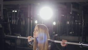 Mulher da aptidão que faz ocupas do barbell em um gym video estoque