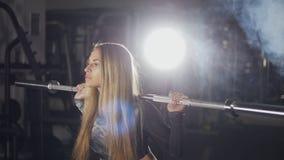 Mulher da aptidão que faz ocupas do barbell em um gym vídeos de arquivo