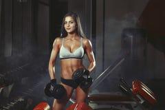 Mulher da aptidão que faz um exercício da aptidão com pesos no gym fotografia de stock